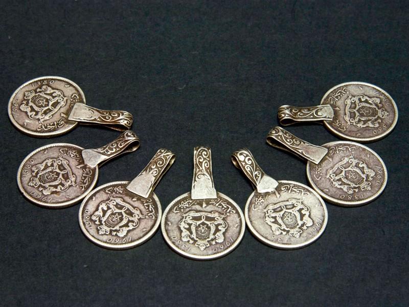 Seven Mohammed V silver coin pendants
